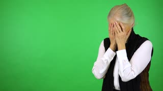 An elderly woman cries with hands over her face - green screen studio