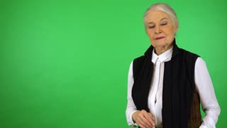 An elderly woman extends her hand to the camera - green screen studio