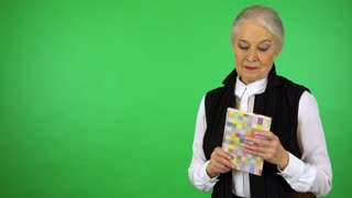 An elderly woman holds a book, smiles at it and at the camera - green screen studio