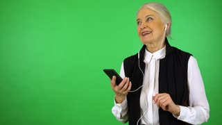 An elderly woman listens to music on a smartphone with a smile - green screen studio