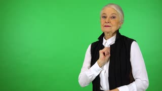 An elderly woman points at the camera and smiles - green screen studio