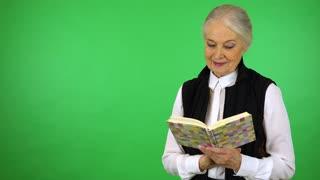 An elderly woman reads a book - green screen studio