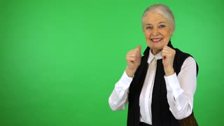 An elderly woman smiles and shows a double thumb up to the camera - green screen studio