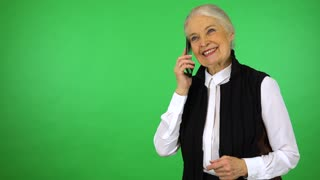 An elderly woman talks on a smartphone with a smile - green screen studio
