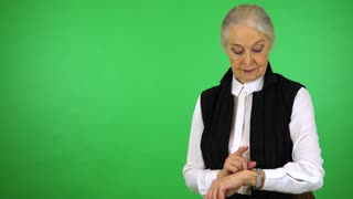 An elderly woman taps her watch, points somewhere and looks at the camera - green screen studio