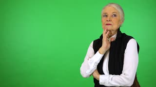 An elderly woman thinks about something - green screen studio