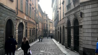City Bergamo in Italy people walk in historical narrow street