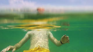 Man swims in the sea near beach in holiday resort (under water shots)