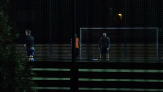 Men play football on a pitch in the night - a high railing in the foreground