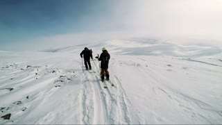NIKKALUOKTA, SWEDEN - APRIL 22, 2017: Man skier is on the top of the mountain with friends and they get ready for skiing - sunny day - first person view