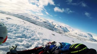 NIKKALUOKTA, SWEDEN - APRIL 22, 2017: Man skier waits with friends for helicopter landing on the mountain and then he boards the helicopter - first person view