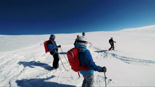 NIKKALUOKTA, SWEDEN - APRIL 22, 2017: Man skier waits with friends in the middle of hill and they get ready for skiing - sunny day - first person view