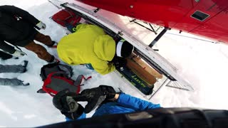 NIKKALUOKTA, SWEDEN - APRIL 22, 2017: Men skiers prepare for a helicopter departure from mountain - man takes down his backpack - first person view