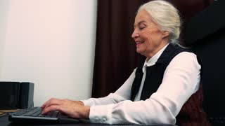 Old happy caucasian woman works on computer in home and she rejoices