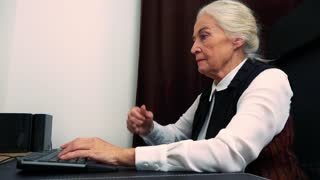 Old unhappy caucasian woman works on computer in home and she is angry
