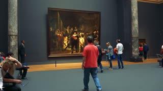 People look at and take photos of a painting in a museum, other people sit on benches on the left