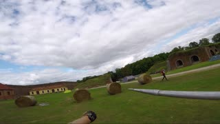 POV - a man at a race hits a hay bale with a javelin, returns the javelin and runs on