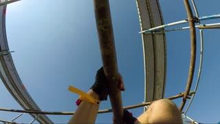 POV - a man climbs a bar upside down at a race