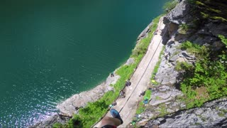 POV - a man walks on a rope from one side of a cliff to another