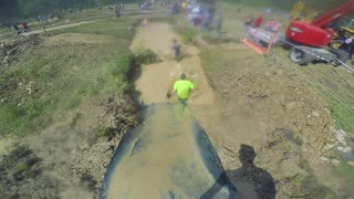 POV GoPro - a man slides into water at a race and pulls himself up on a rope
