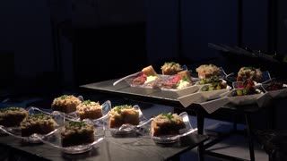 Restaurant meals on tables in a dark room - a man finishes preparations in the background