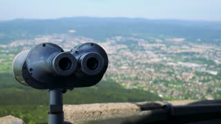 Sightseeing binoculars with oculars to the camera, a town and a forest in the blurry background