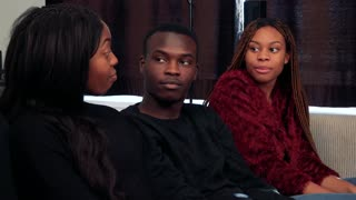 Three african friends talk about something in living room