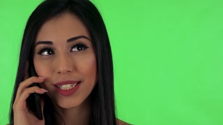 young attractive asian woman phone and smiles - green screen studio - closeup