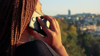 Young beautiful black woman phone - city in the background - closeup