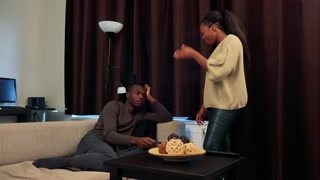 Young black man watches TV and ignores his girlfriend, she is angry at him