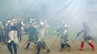 Warriors in mediaeval costumes with weapons march in dense smother