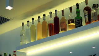 White shelf with bottles of drinks in bar