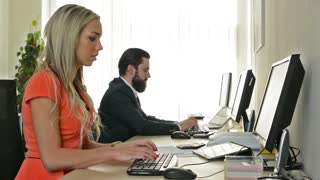 woman and man work on desktop computer and are angry in the office (workers)