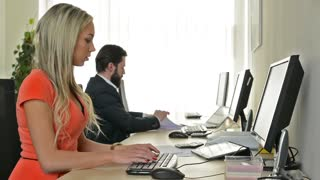 woman and man work on desktop computer and talk about document in the office