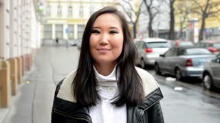 young attractive asian woman agree - urban street with cars - city