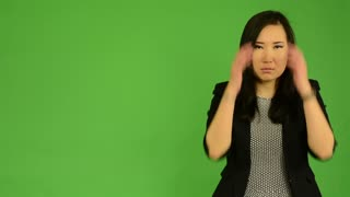 young attractive asian woman is afraid - green screen studio