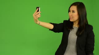 young attractive asian woman photographs with smartphone (selfie) - green screen