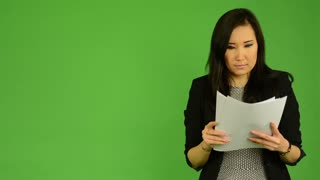 young attractive asian woman reads documents (papers) - green screen studio