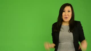 young attractive asian woman rejoices - green screen studio