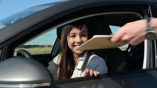 young attractive happy woman signs the contract - buys the new car - obtains key