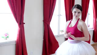 young attractive shy ballerina smiles to camera - interior - red curtain