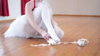 young ballerina puts on ballet shoes and ballerina ties shoes