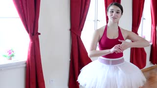 young ballerina talks to camera - hall - red curtain