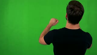 young bearded man rejoices - shot on back (man looks to screen) - green screen