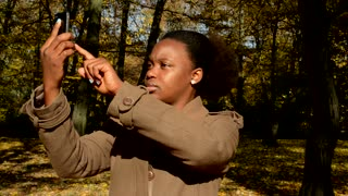 Young beautiful african girl stands in woods, makes a photos of nature