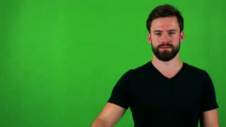 young handsome bearded man waves with hand - green screen - studio