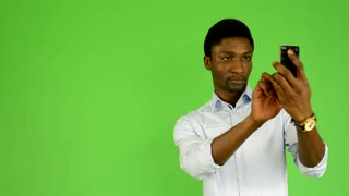 young handsome black man photographs with smartphone - green screen studio