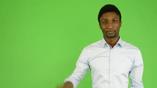 young handsome black man waves with hand  - green screen - studio