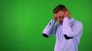 young handsome business man is afraid (man covers his ears) - green screen