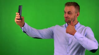 young handsome business man photographs with smartphone (selfie) - green screen